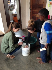 Emma and Jeorgia serve the kids porridge while I hand out sandwiches alongside another volunteer.